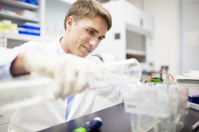 Male student in research lab pouring liquid from one container to another
